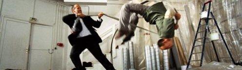 Jason Statham öltönyben épp kigáncsol valakit egy csővel
